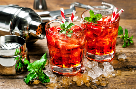 Red drink with strawberry, mint leaves, ice. Cocktail with campari, aperol, gin, liquor, juice, soda water