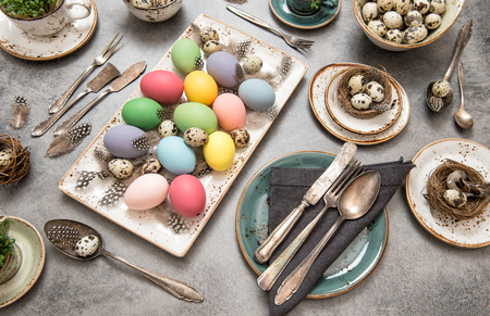 a place of life: Festive table place setting decoration with colored eggs. Easter still life. Top view