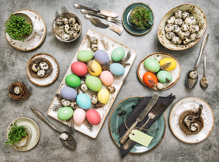 place setting: Easter table place setting decorated with colored eggs. Vintage style toned picture