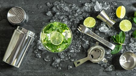 Glass of cocktail with lime, mint, ice. Drink making bar tools, shaker, ingredients