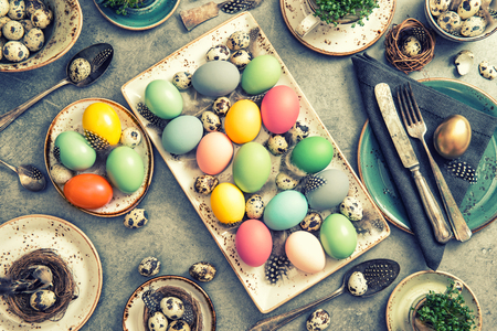 Easter dinner table decoration with colored eggs. Vintage style toned picture