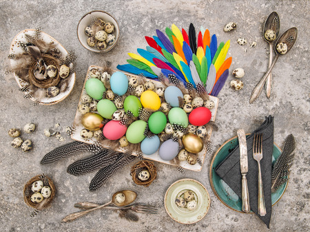 vintage cutlery: Easter table decoration with colored eggs, feathers and vintage cutlery Stock Photo