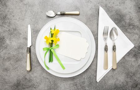 cuchillo: decoración de la mesa de la primavera con las flores del narciso. Placas blancas, tenedor, cuchillo en la placa de piedra gris