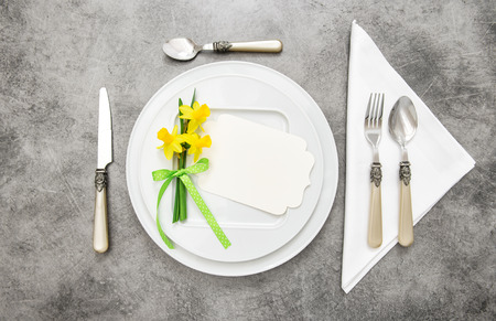 Spring table decoration with narcissus flowers. White plates, fork, knife on grey stone plate