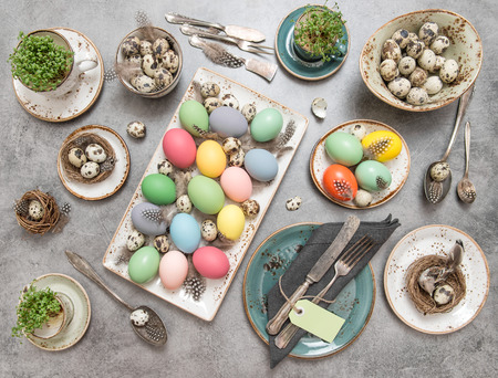 vintage cutlery: Easter still life. Festive table place setting decoration with colored eggs and vintage cutlery