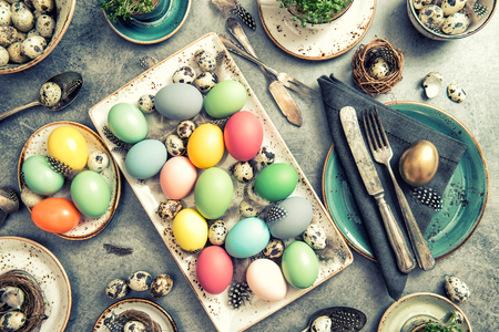 place setting: Easter table place setting decoration with colorful eggs. Vintage style toned photo
