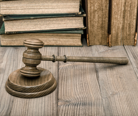 auctioneer: Judges gavel with soundboard and old books on wooden background. Auctioneer hammer