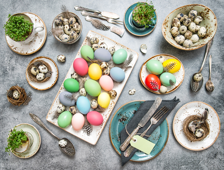 vintage cutlery: Easter table decoration with colored eggs and vintage cutlery. Retro style toned picture