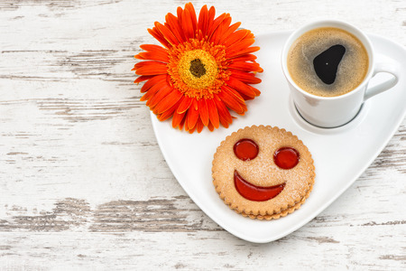 smiled: Cup of black coffee with smiled cookie on wooden background. Funny breakfast Stock Photo