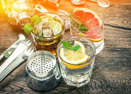 drinks on bar: Fruit drinks with ice. Cocktail making bar tools. Vintage toned picture Stock Photo