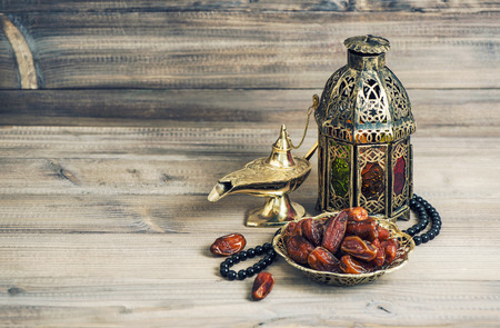 Arabian lantern, golden lamp and fruits. Islamic holidays decoration. Eid mubarak. Vintage style toned picture