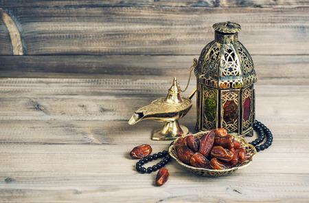 dattes: Arabian lantern, golden lamp and fruits. Islamic holidays decoration. Eid mubarak. Vintage style toned picture