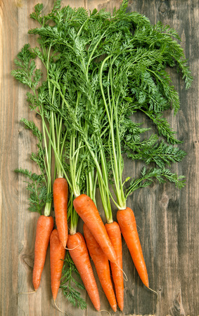 rustic food: Carrot roots over rustic wooden background. Healthy organic food Stock Photo