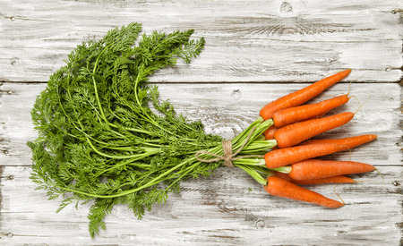 rustic food: Carrots bunch on bright rustic wooden background. Organic food concept Stock Photo
