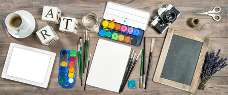 no name: Artistic workplace. Watercolor, brushes, digital tablet pc, chalkboard, vintage camera no name, office supplies tolls accessories Stock Photo