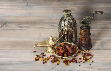 dattes: Vintage oriental latern table de décoration et de l'usine. Raisins et dates de fond en bois Banque d'images