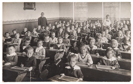 family history: Group of children and teacher in the classroom. Retro picture of classmates in the school. Vintage photo with original film-grain, blur and scratches from ca 1932 Stock Photo