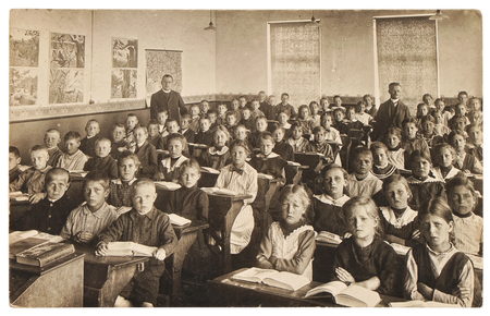 Retro picture of classmates. Group of children in the classroom. Vintage photo from about 1936 with original film-grain, blur, scratches Stock Photo