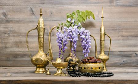 葡萄酒阿拉伯水罐,花瓶,灯,茶壶,伊斯兰念珠。水果和鲜花。东方假日装饰。斋月贾巴雷姆