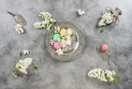 antique dishes: White lilac flowers and macaroon cakes. Antique silver dishes. Vintage style background