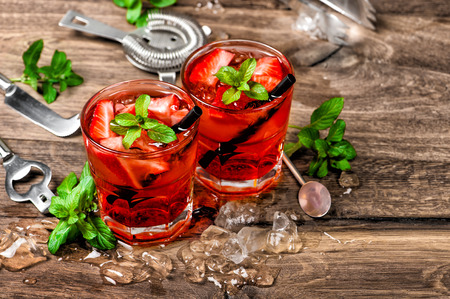 non alcoholic: Red cocktail with ice, mint leaves and strawberry. Alcoholic and non alcoholic drinks making bar tools
