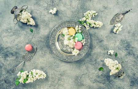 antique dishes: White lilac flowers and macaroon cakes. Antique silver dishes. Vintage style toned picture Stock Photo
