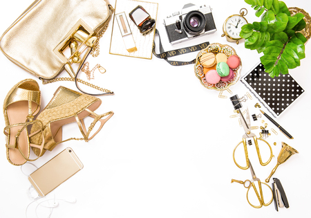 Fashion flat lay for bloggers social media. Feminine golden accessories, bag, shoes, office supplies, vintage no nae photo camera and green plant on white background Stock Photo