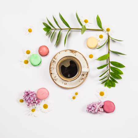 Coffee, french cookies macaroons, spring flowers. Floral flat lay. Minimal concept