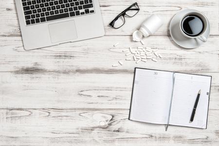 cansancio: el lugar de trabajo de oficina con una taza de café, un portátil y medicina cápsulas. La salud, el estrés y el cansancio concepto