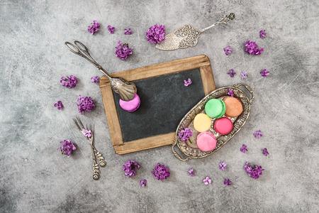 vintage cutlery: Macaroon cookies with lilac flowers. Vintage cutlery and chalkboard