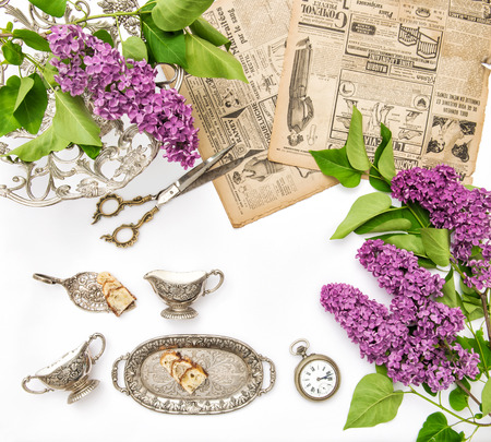 antique dishes: Lilac flowers, vintage cutlery and dishes, antique accessories. Styled fashion flat lay