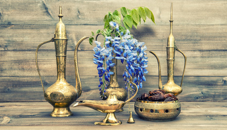holy jug: Antique arabic jug, vase, lamp, tea pot. Fruits and flowers. Golden oriental decorations. Vintage style toned picture