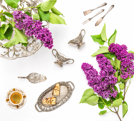 antique dishes: Coffee with cake and antique silver dishes. Lilac flowers. Flat lay background