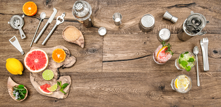 Alcoholic and nonalcoholic drinks with ice. Cocktail making bar tools, shaker, glasses. Flat lay.Top view