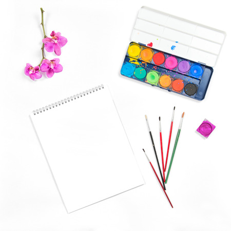 flat brushes: Flat lay with sketchbook, watercolor, brushes, paper, orchid flower on white background