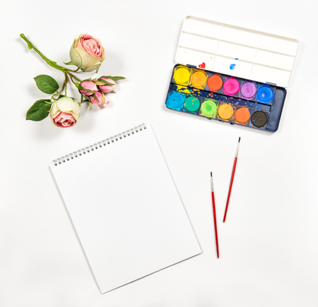 flat brushes: Flat lay with sketchbook, watercolor, brushes, paper, rose flowers on white background