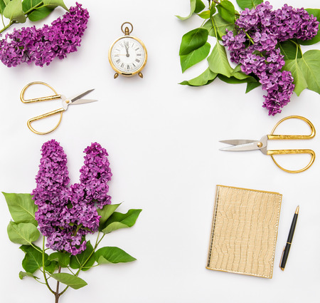 Lilac flowers, diary notebook, golden office supplies. Flat lay Stock Photo