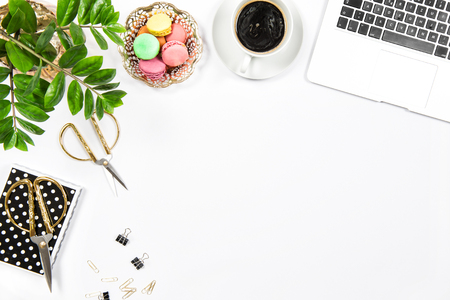 Workplace with coffee, cookies, laptop computer and green plant on white table background. Top view. Flat lay Standard-Bild