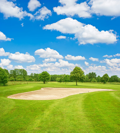 Green golf course field and blue cloudy sky. European nature landscape Stock fotó