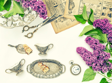 styled: Lilac flowers, antique cutlery and dishes. Styled fashion flat lay. Vintage toned picture