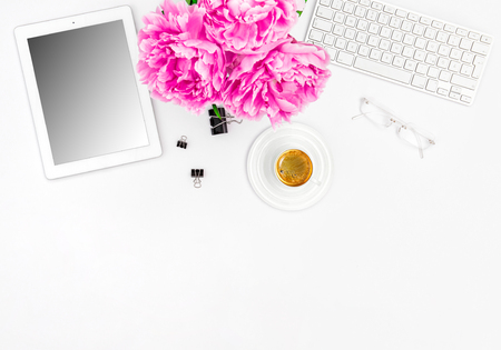 Feminine office workplace with coffee and flowers. Mockup with digital tablet screen Standard-Bild