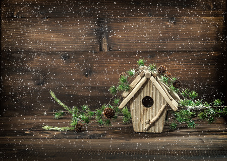 Christmas decoration birdhouse on rustic wooden background.