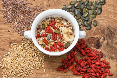 Oatmeal with goji berries, linseed, pumpkinseed. Muesli breakfast on wooden background.