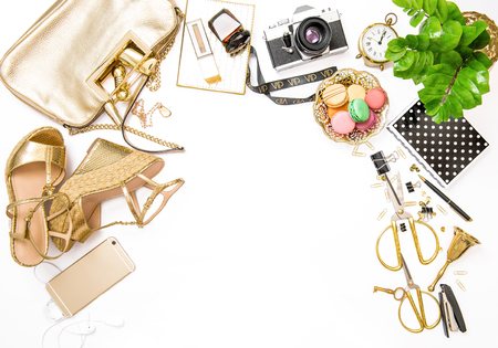 Fashion flat lay. Feminine golden accessories, bag, shoes, office supplies, vintage no name photo camera on white background