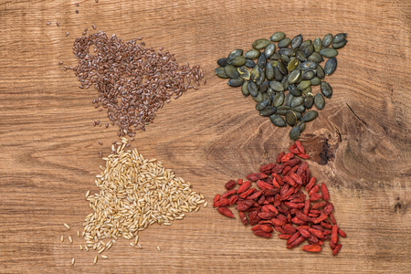 Goji berries, oats, linseed, pumpkinseed on wooden background.