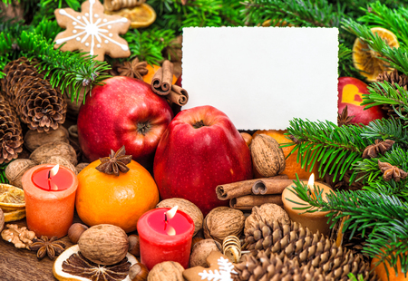 Christmas decoration burning candles and greetings card. Apples, tangerine, nuts, spices and cookies