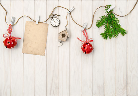 Christmas ornaments with greeting card. Christmas tree branches on bright wooden background