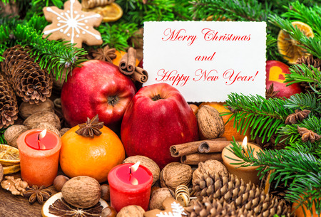 pinecones: Christmas decoration burning candles and greetings card. Apples, tangerine, nuts, spices and cookies. Sample text Merry Christmas Happy New Year!