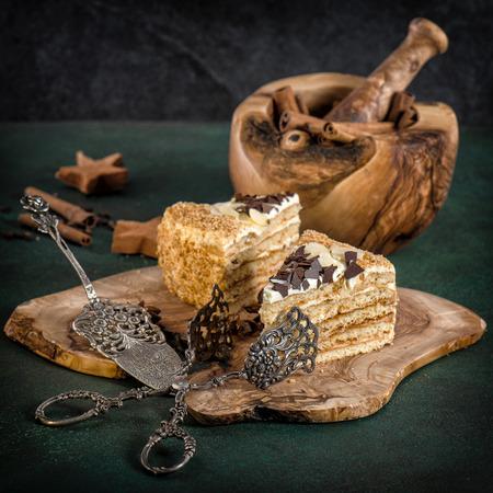 honey cake: Honey cake with vintage tools on dark background. Sweet food. Retro style toned picture