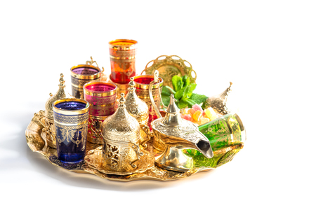 Golden tea service and green mint leaves on white background. Colorful holidays decoration. Ramadan. Eid Mubarak